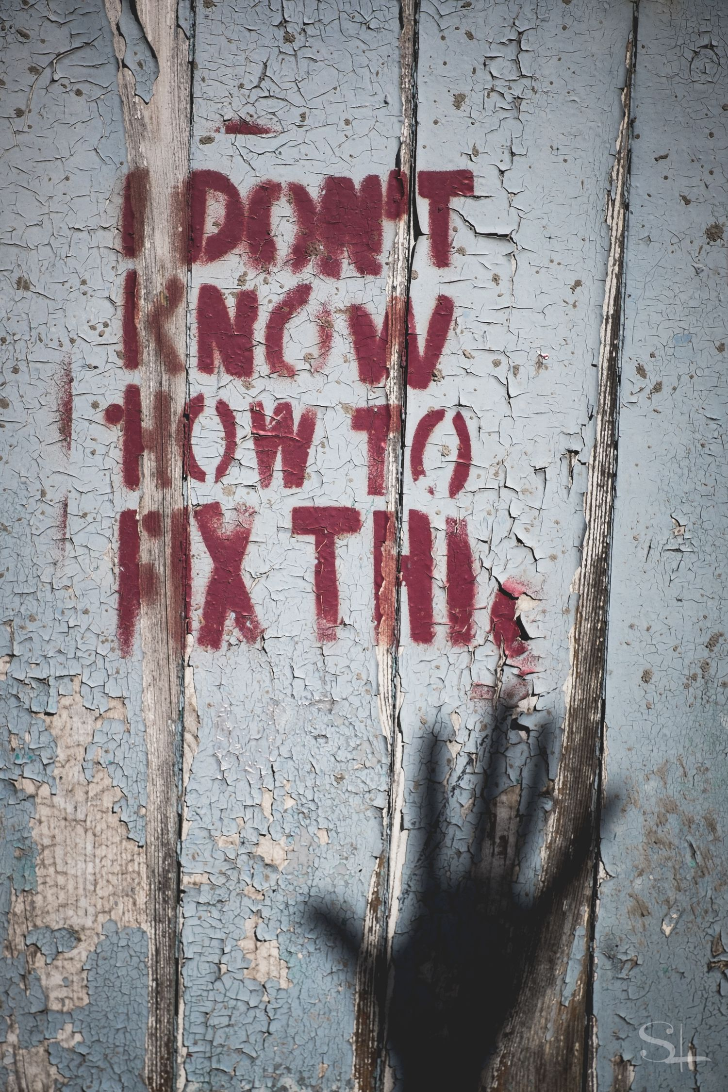 "red stencilled words ""I don't know how to fix this"" on blue chipping paint with a shadow of a open hand at the bottom"