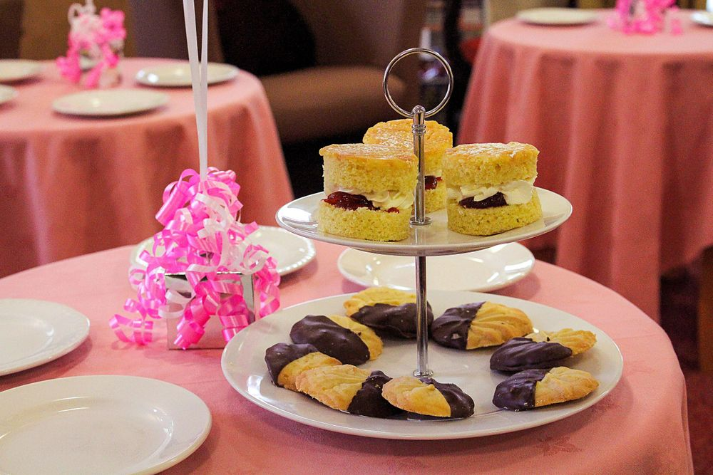 cakes on a cake stand sitting on a table ready for the macmillan tea party