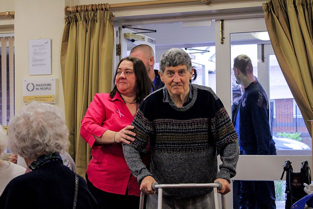 man with zimmer frame and other guests arriving for the macmillan tea party