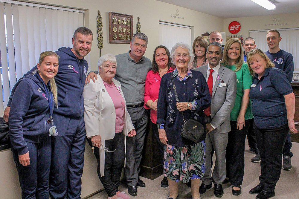 everyone poses for a group photograph during the macmillan tea party