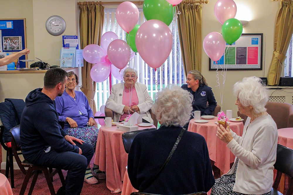 guests at the macmillan tea party surrounded by balloons and sitting around the table