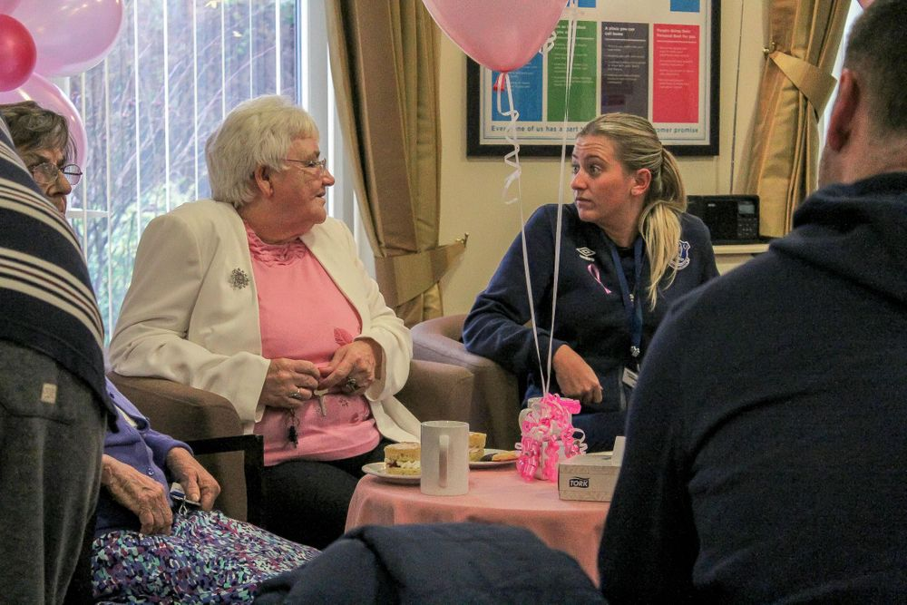 elderly lady chats with a care worker at the charity tea party