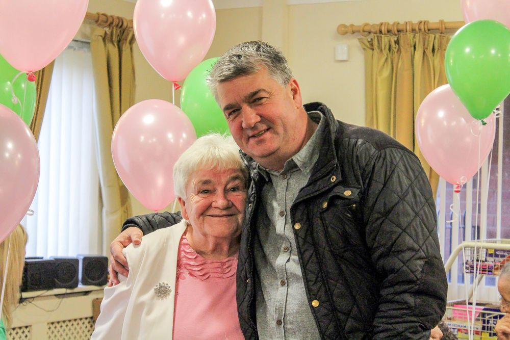 elderly lady gets a hug from former everton footballer Ian Snodin at the macmillan tea party