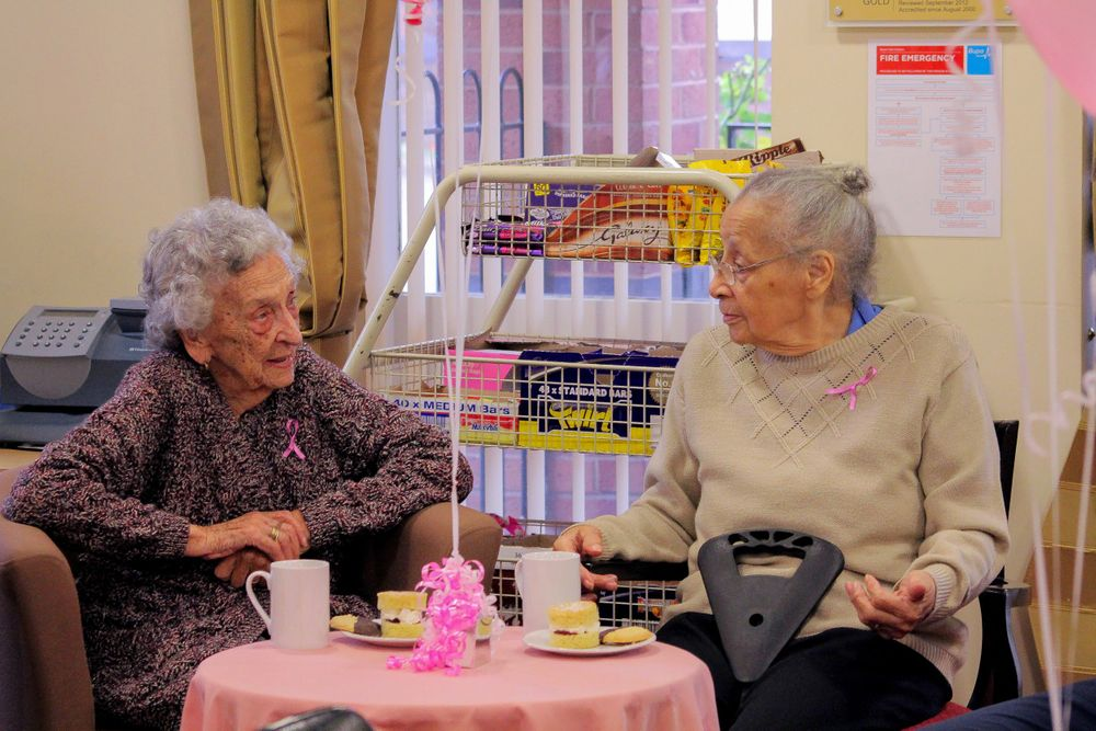 2 elderly ladies drinking tea and eating cake at the macmillan charity event