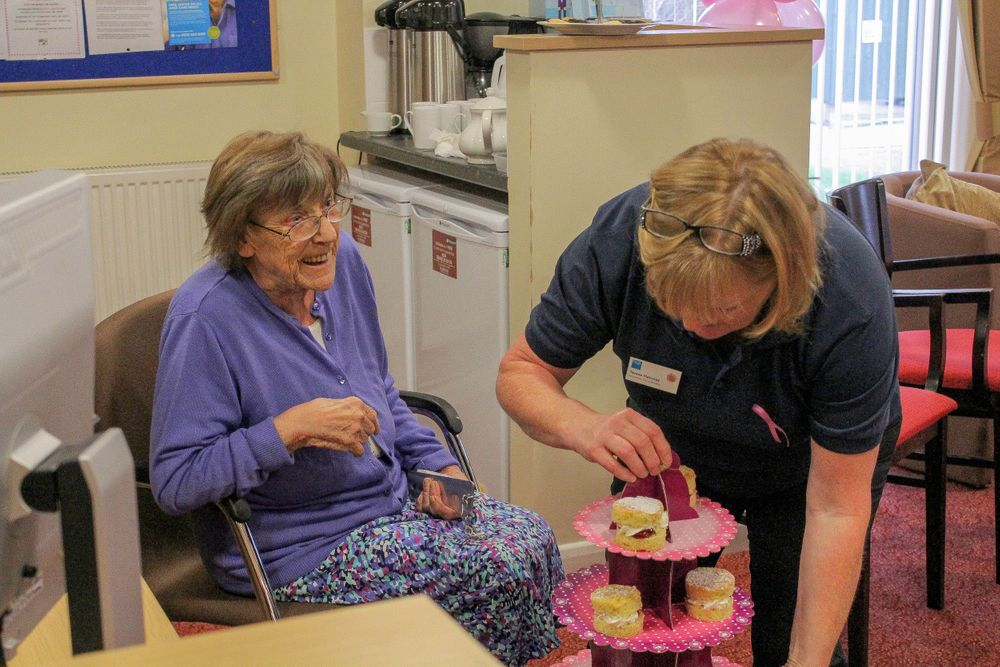 care worker puts a cake stand full of treats down in front of one of the elderly ladies at the macmillan tea party