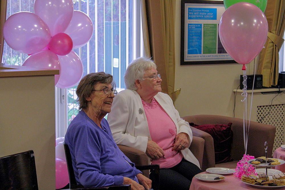 2 elderly ladies surrounded by balloons at the macmilllan charity tea party