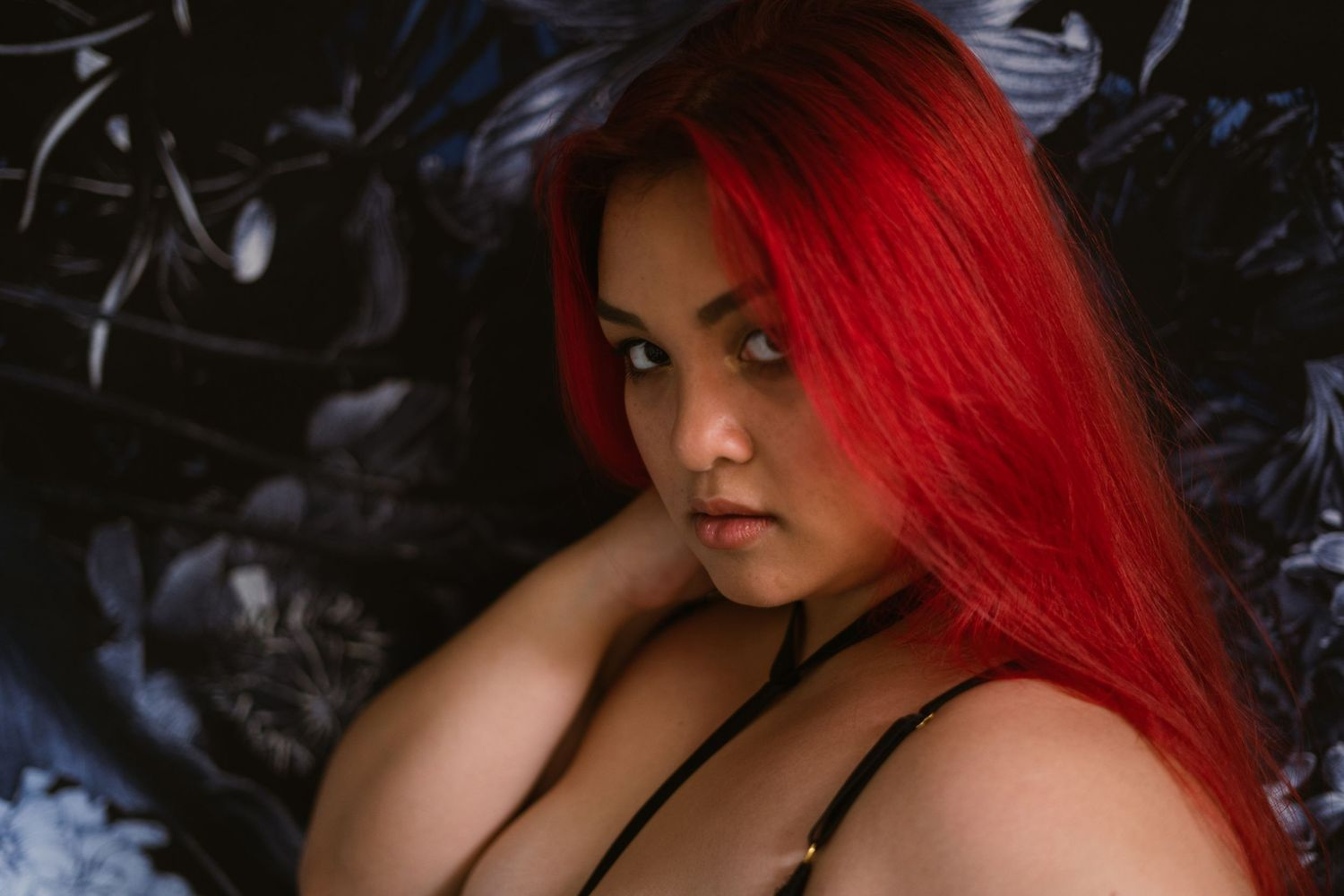 a woman with red hair and medium skin looks intensely at the viewer