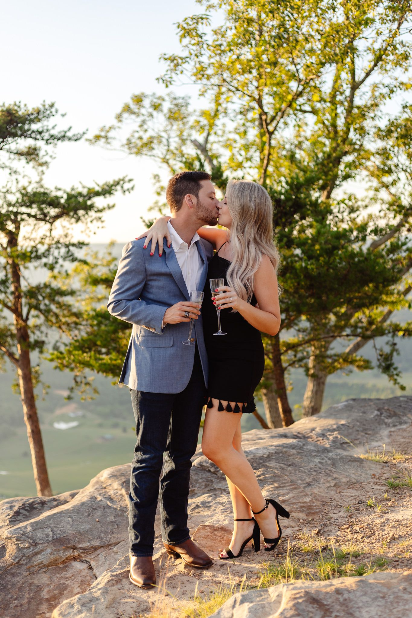 A couple kisses on top of a mountain after their surprise proposal captured by engagement photographer Sarah Swainson.