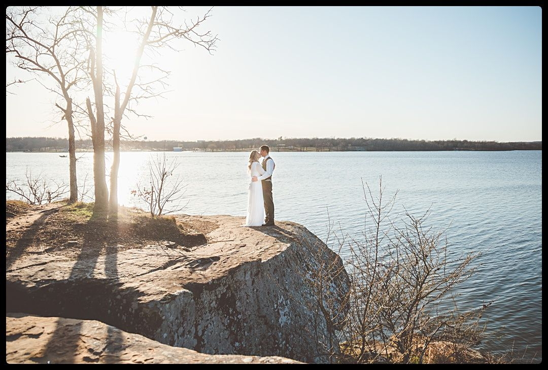 Bride and groom kissing on a cliff overlooking a lake
