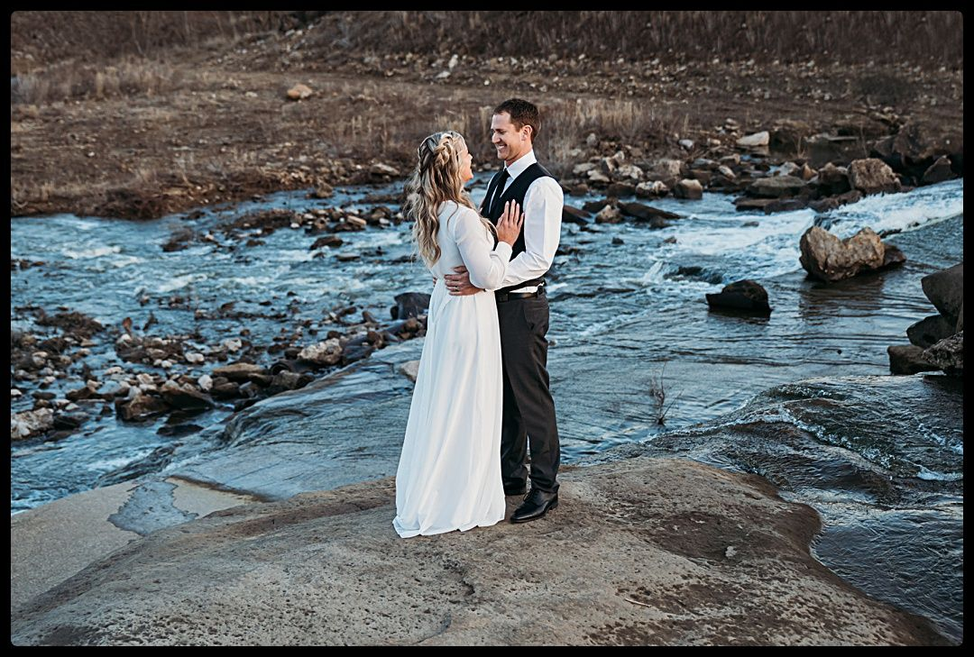 Bride and groom embracing in front of waterfall