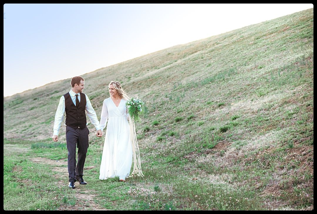 Bride and Groom walking through green field