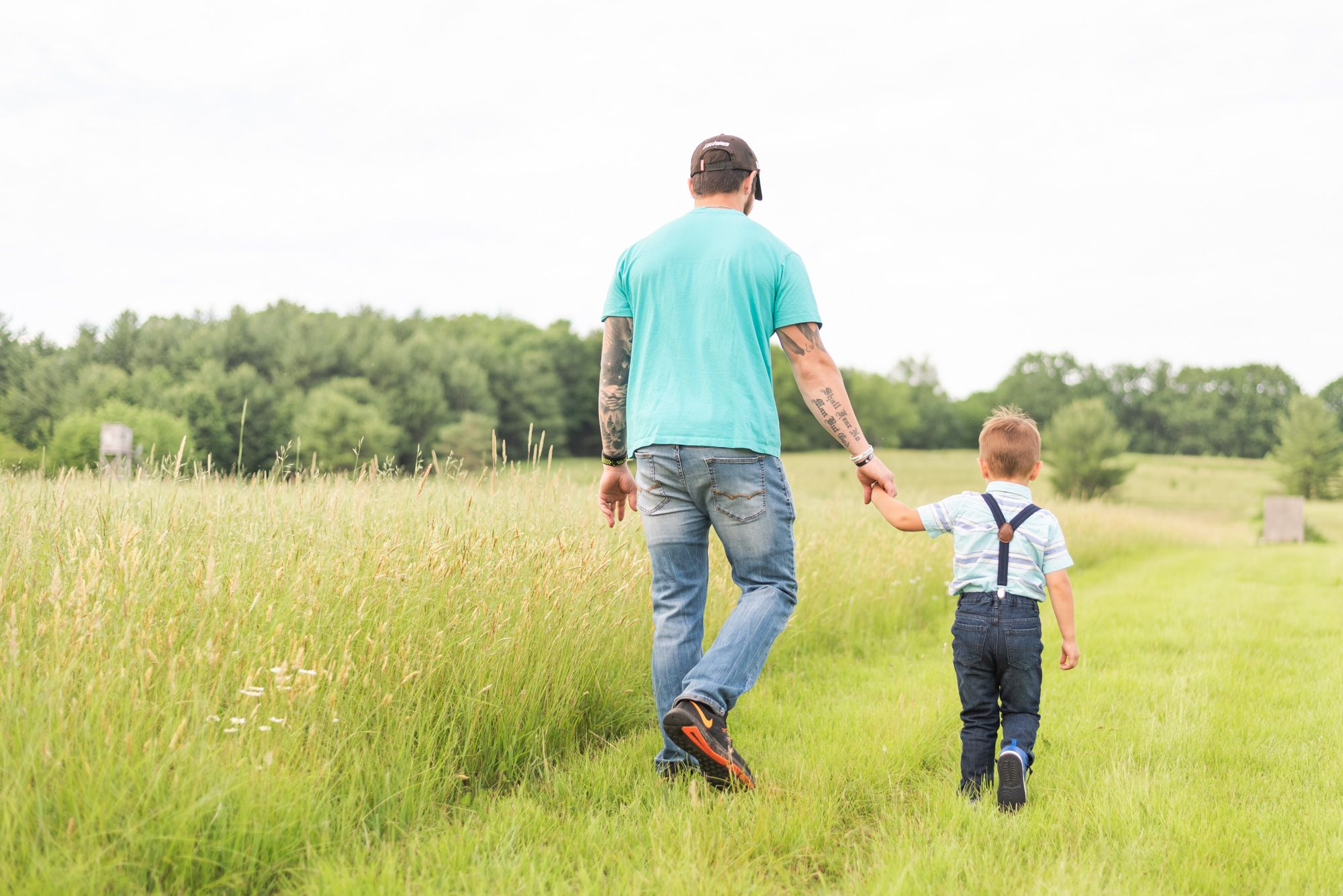 Father and son walking away through field in Clarion Pennsylvania