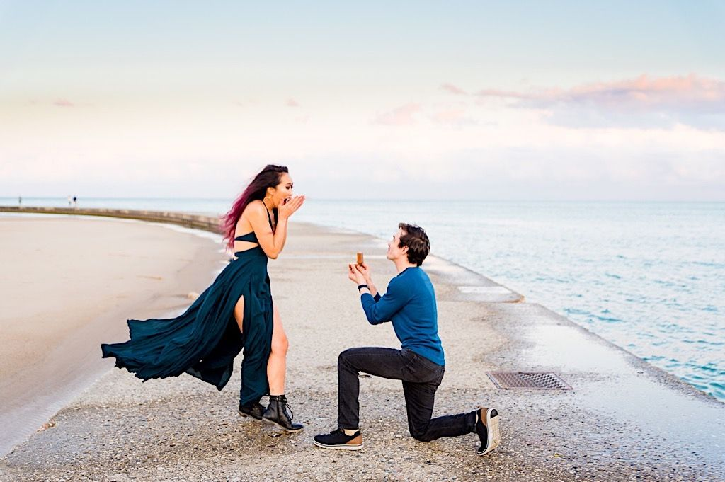 woman is shocked to see her boyfriend on one knee proposing on North Avenue Beach