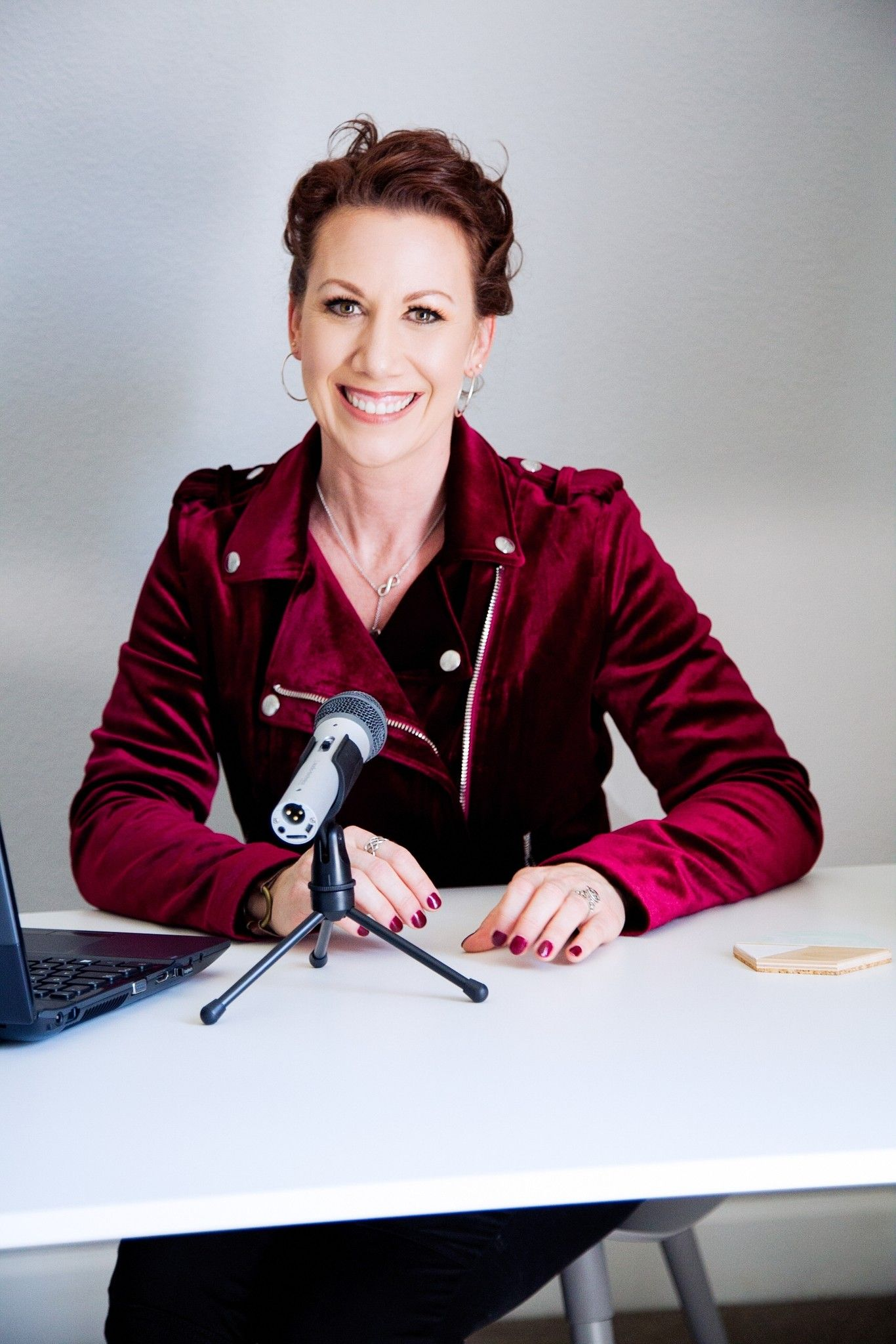 Business coach in red moto jacket recording a podcast