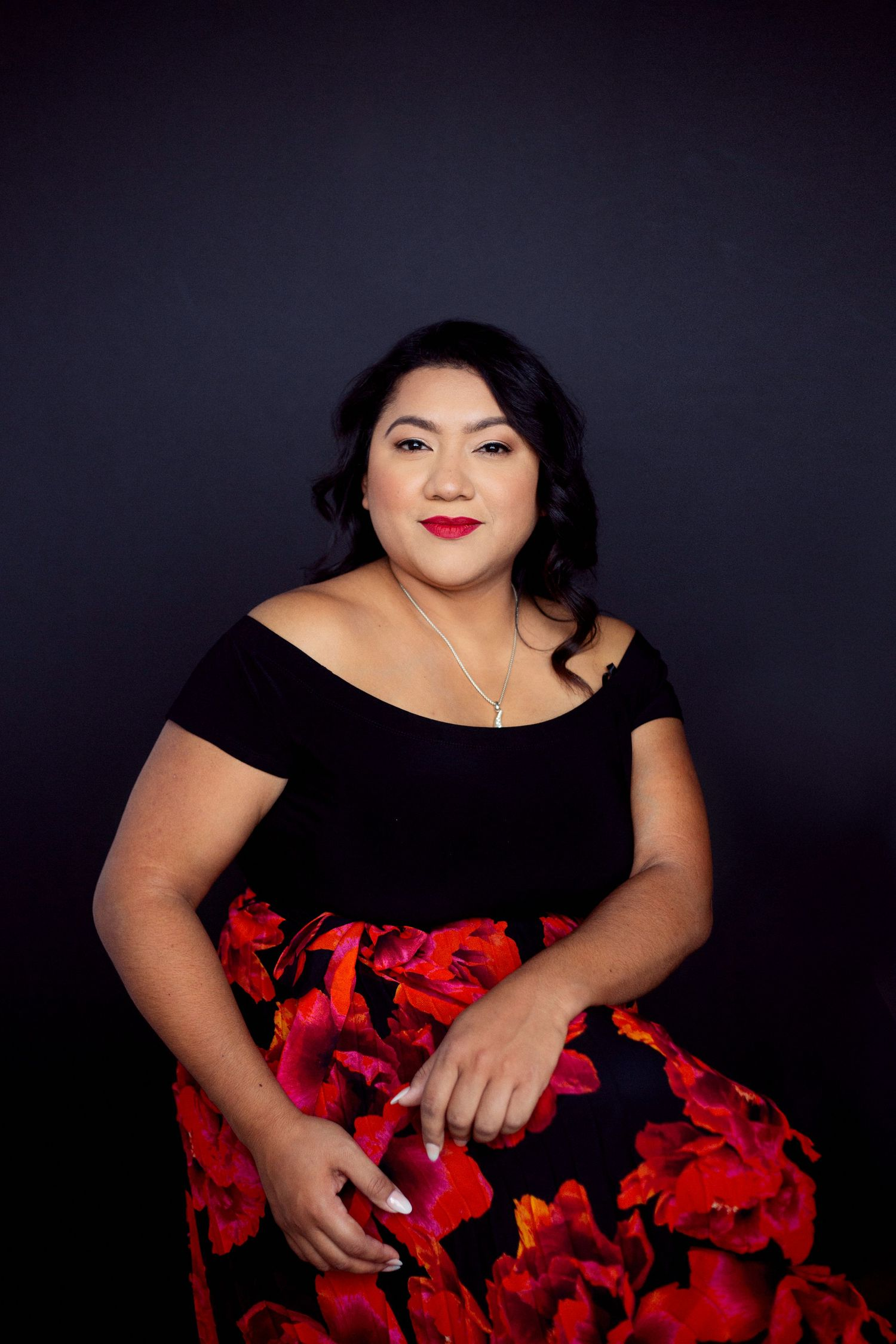 Latina in black and red dress posing for portrait on black background