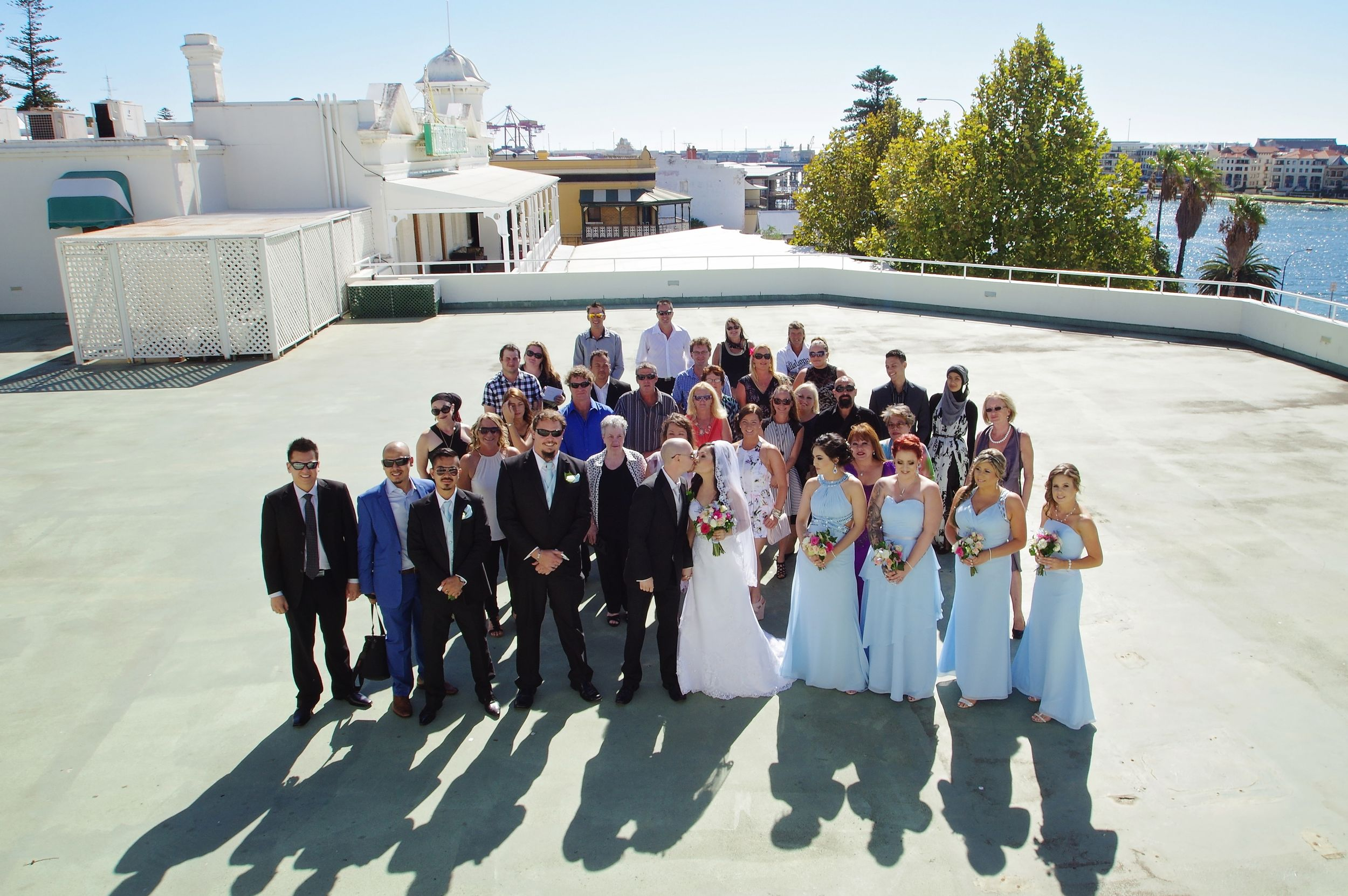 group shot of bride and groom and guests on rooftop