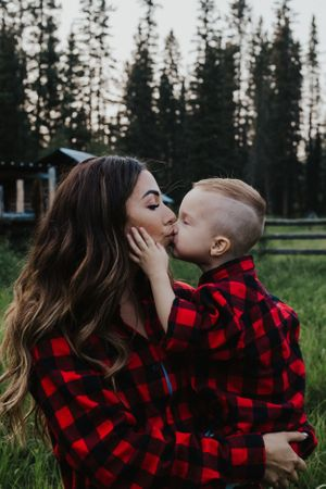 Young son in plaid kisses his mom in matching plaid shirt