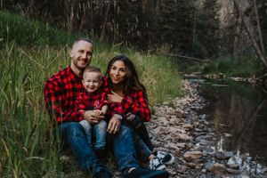 Family in red plaid smile while sitting by Alberta river
