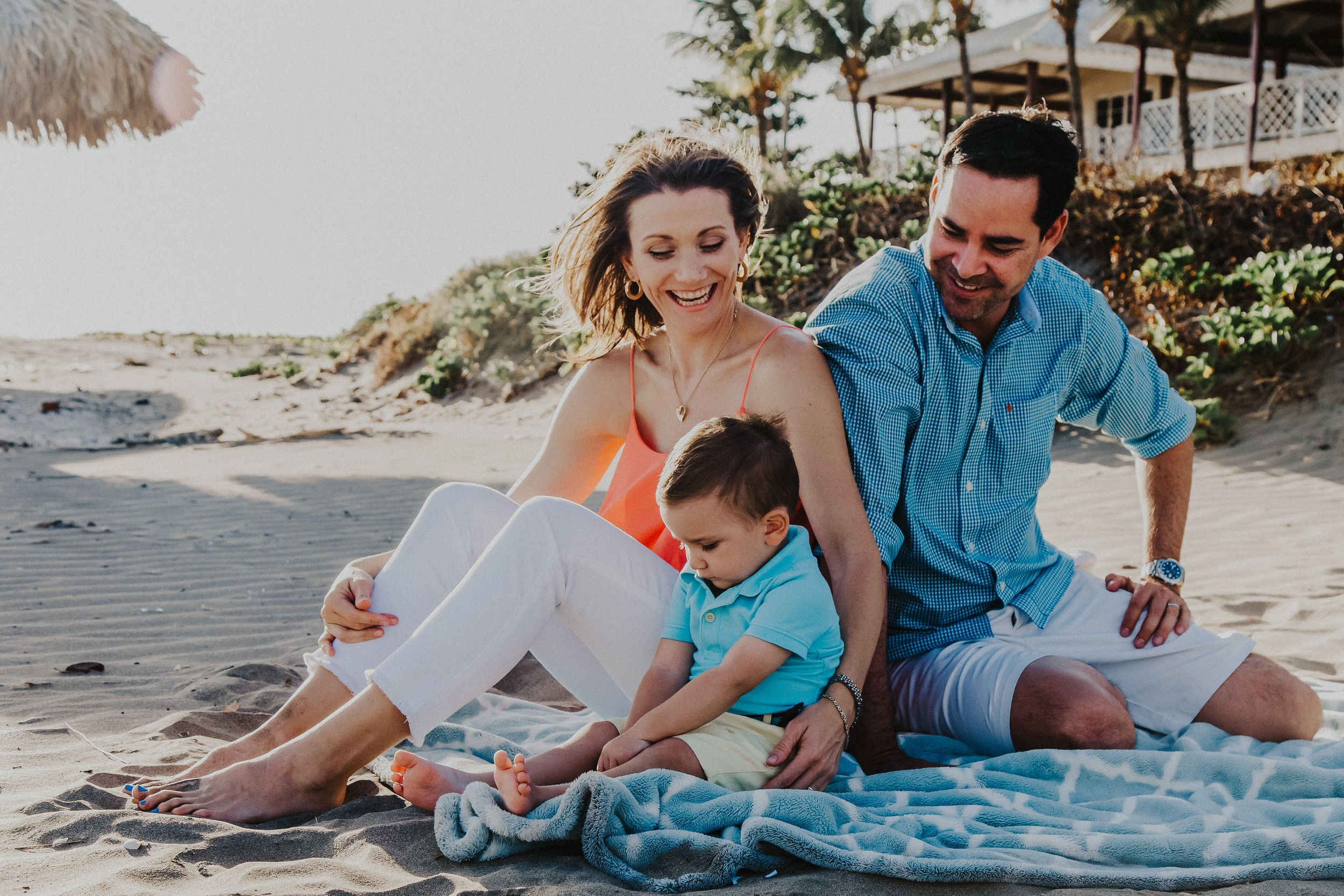 Family of 3 sit on a tropical beach smiling