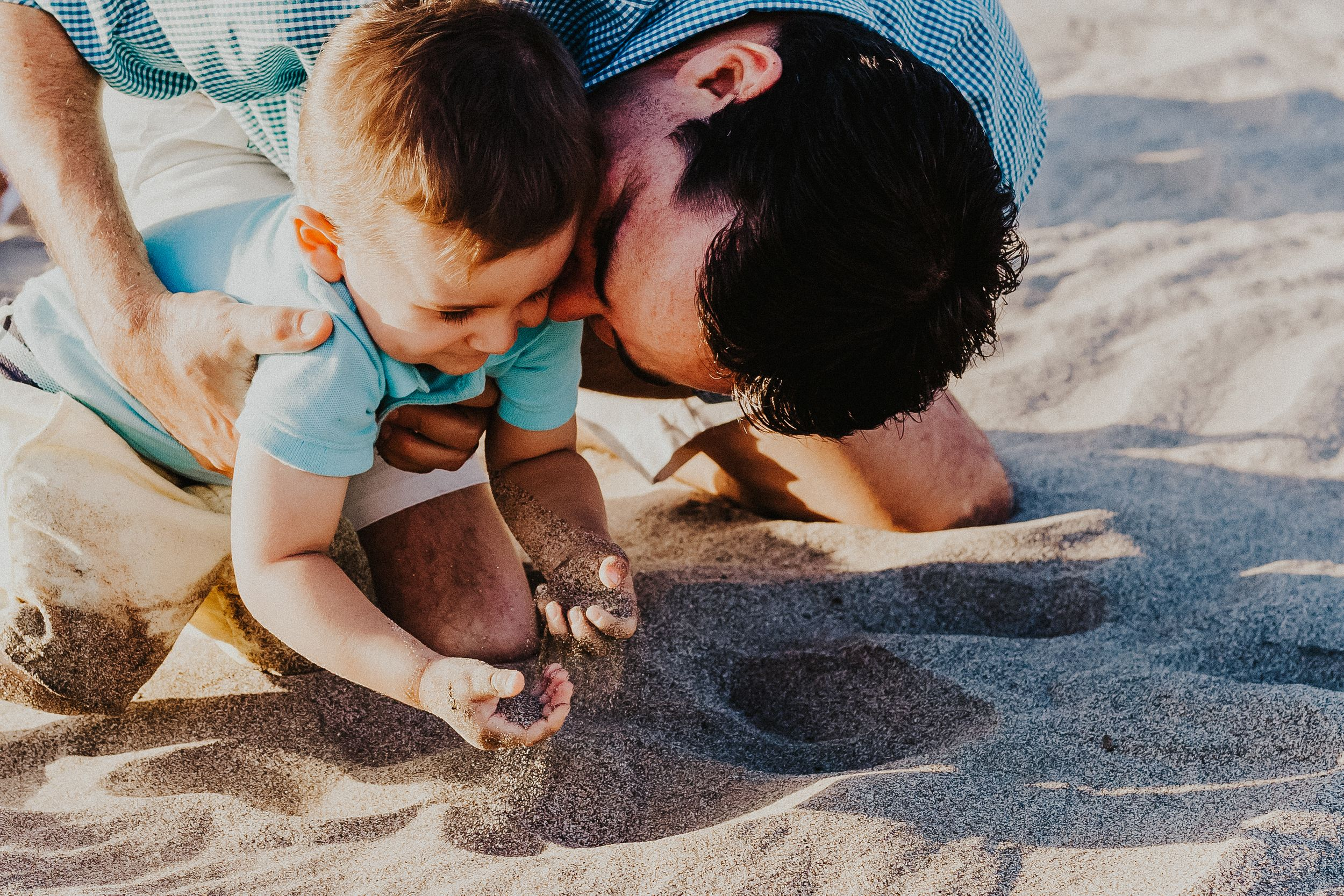 Dad kisses son on the cheek while he is playing in the sand