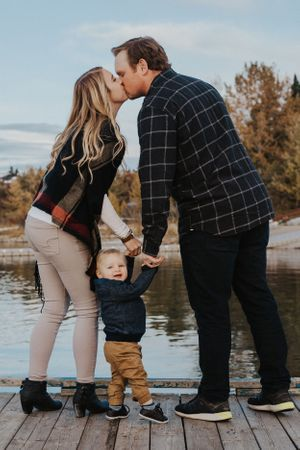 Couple kiss while holding baby boy's hands