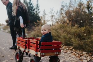 Couple pull son in red wagon during family photos in Calgary