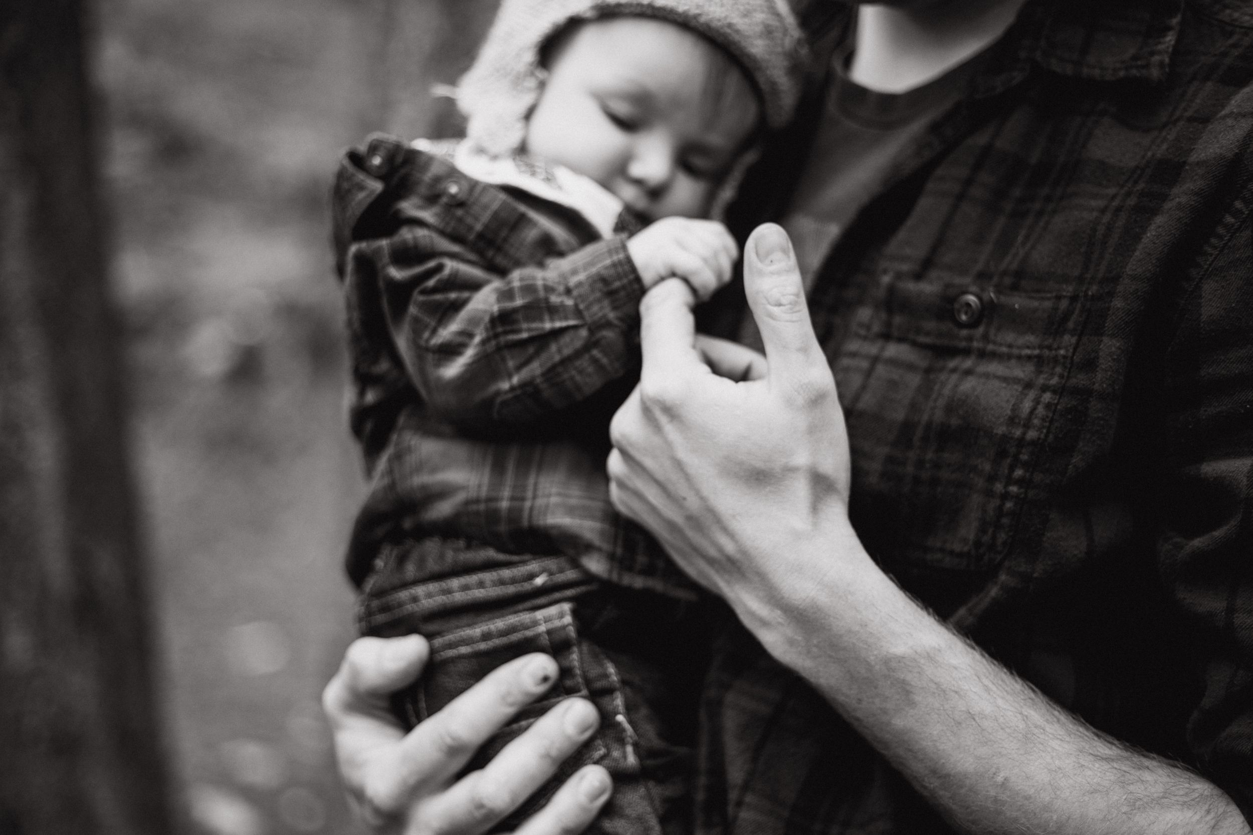 Baby boy grabs onto his dad's finger in black and white photo