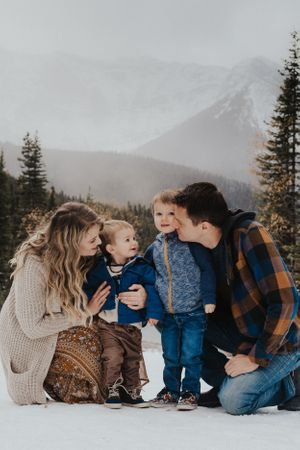 Family of four cuddle in front of Kananaskis mountains