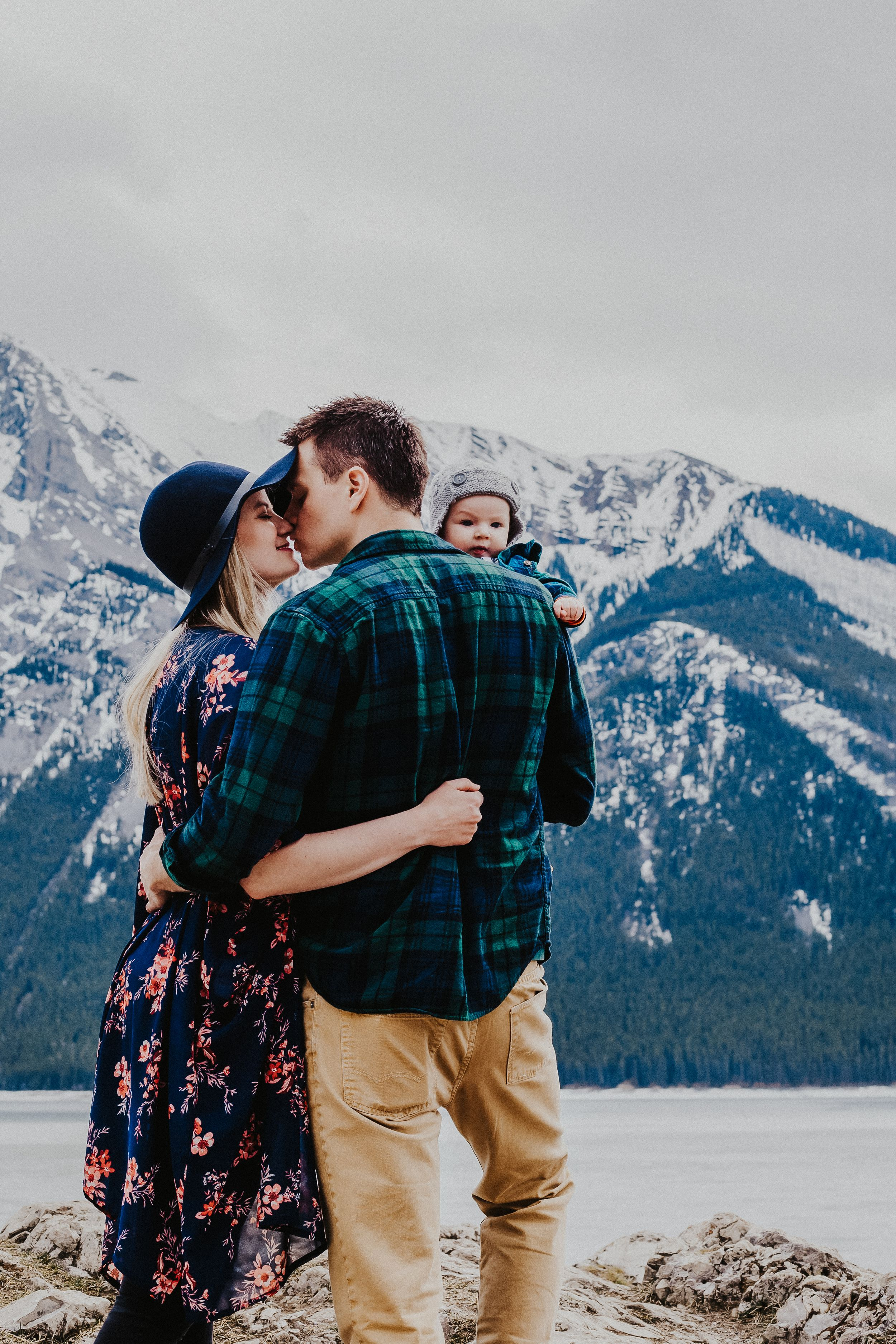 Couple and their baby snuggle and smile in front of the Banff mountains