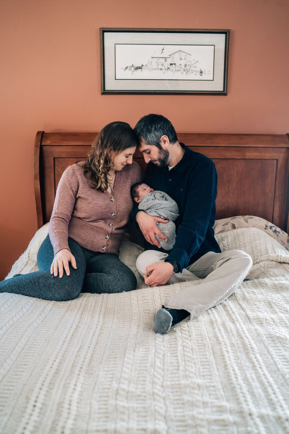 parents snuggling their baby in their bed