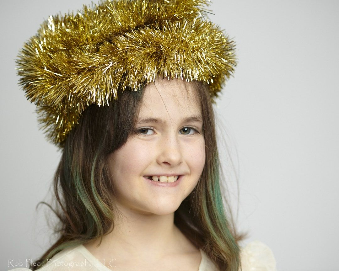 portrait of girl wearing headdress made of gold garland from the Christmas tree