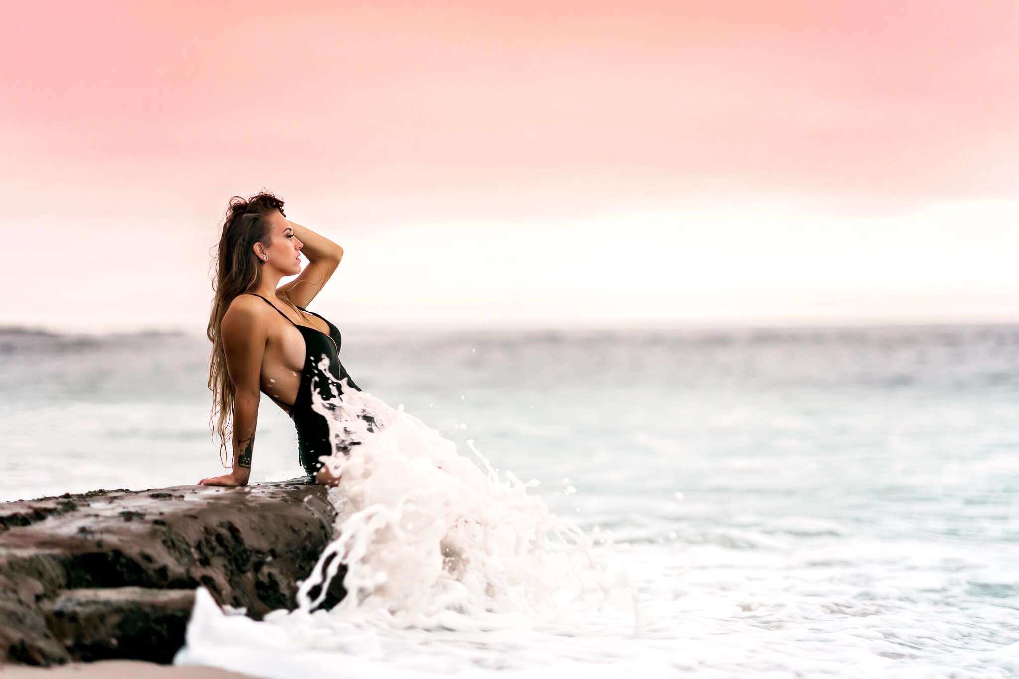 brunette woman on beach at sunset with wave boudoir photography san diego ca