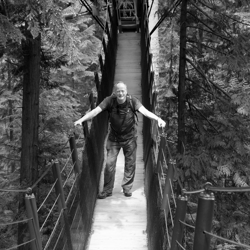 Tim Stewart, Wedding Photographer standing on a rope bridge in black and white.