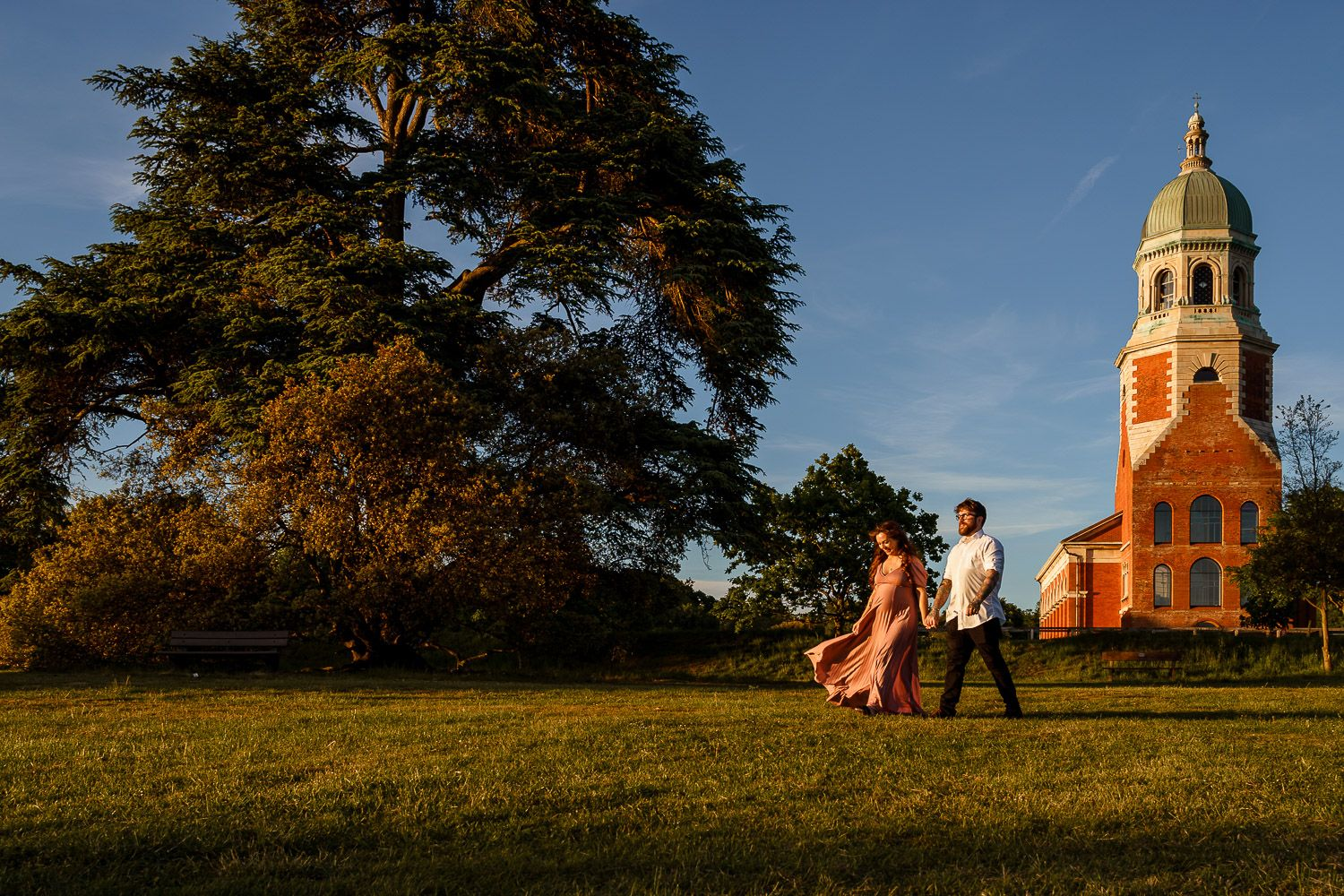 Husband and his pregnant wife walking in front of the chapel at Royal Victoria Country Park in Southampton.