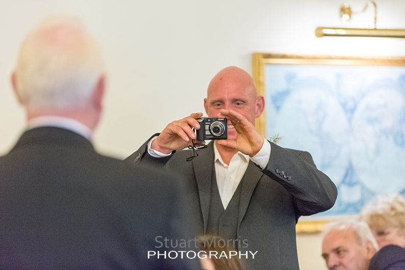 wedding guest takes a photo of the groom and his father
