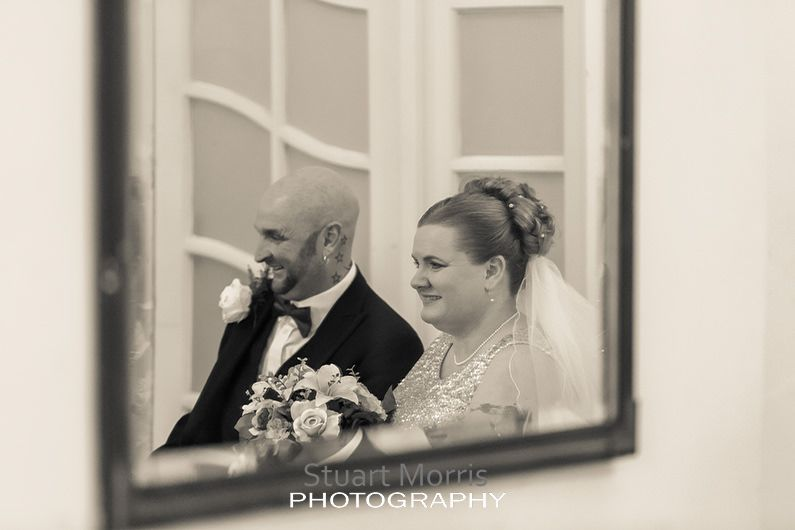 bride and groom sit down during the ceremony reflected in a mirror