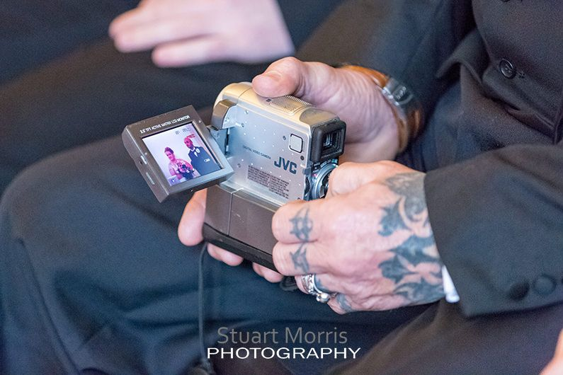 wedding guest records the ceremony on a camcorder with a flip out screen