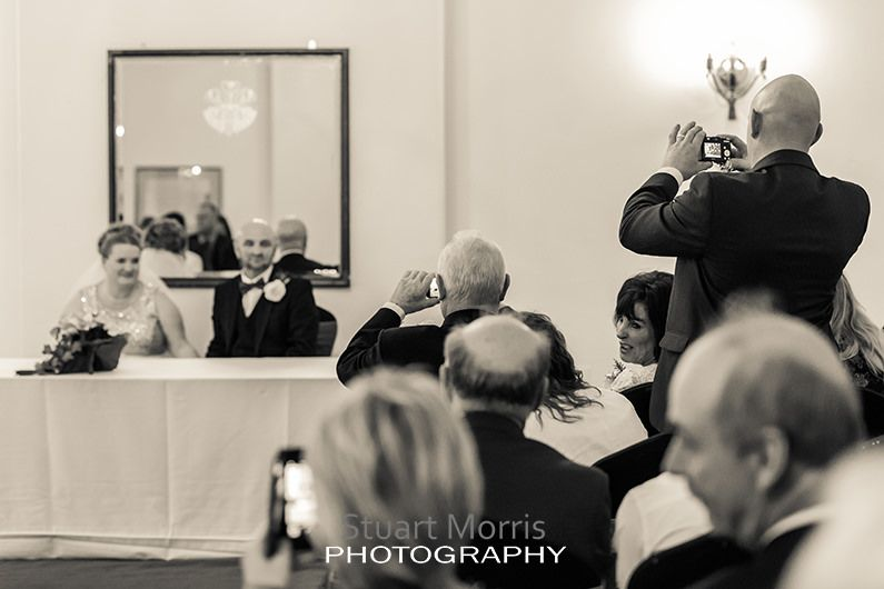 wedding guest stands up to take a photograph of the bride and groom as they sign the wedding register