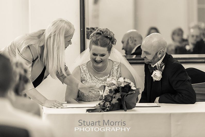 bride sits smiling next to the groom as the registrar shows them where to sign the wedding register