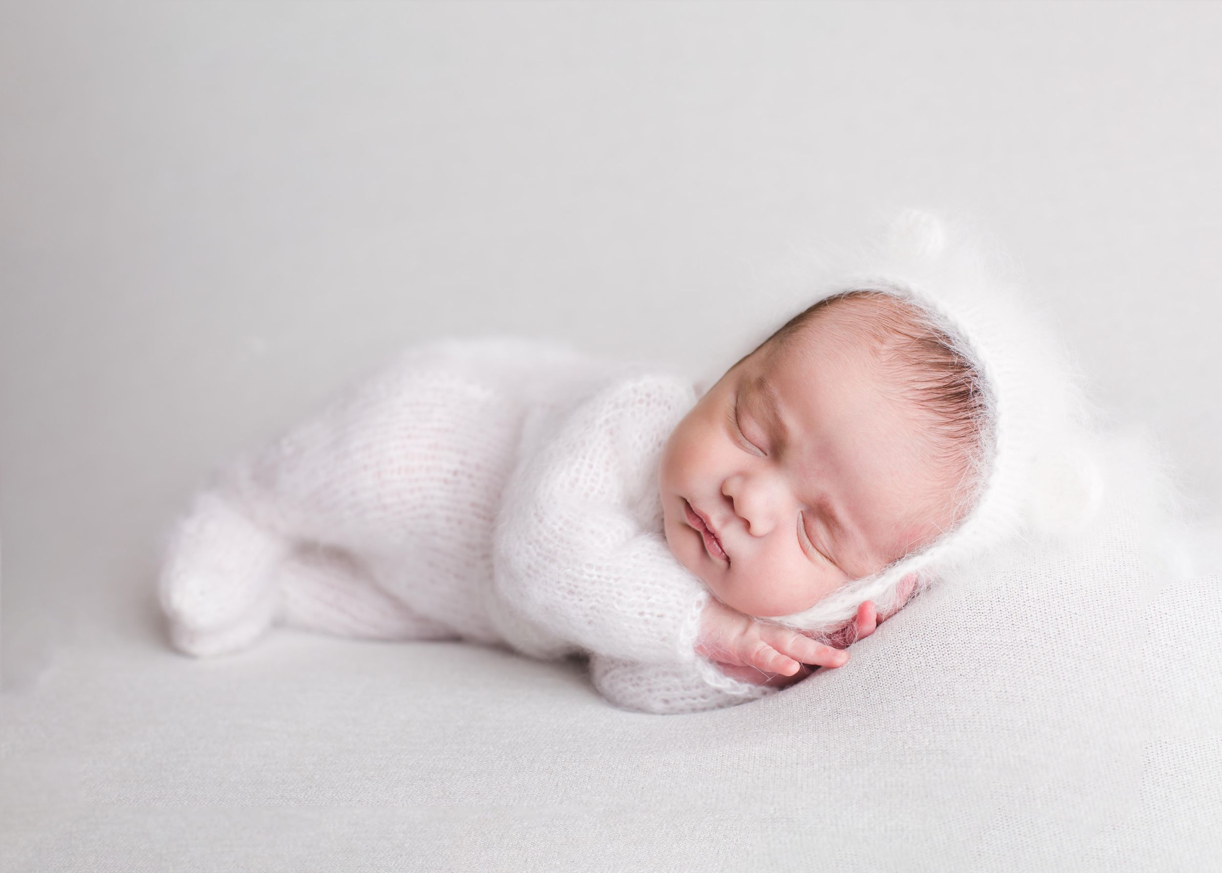Newborn baby laying on a white blanket in a cute white knit outfit - Newborn photography in Penticton