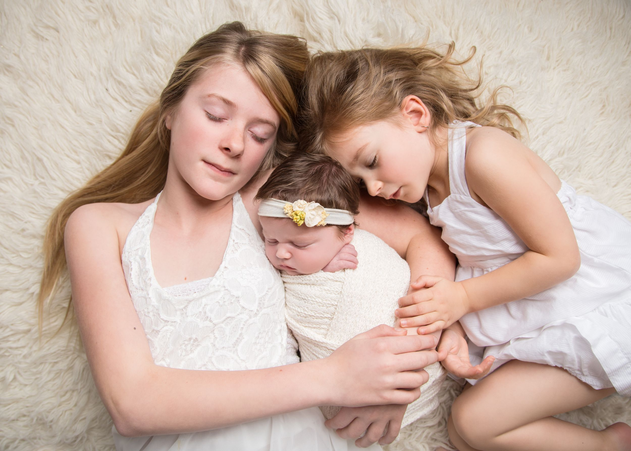 Newborn baby girl laying with siblings - Newborn photography in Penticton