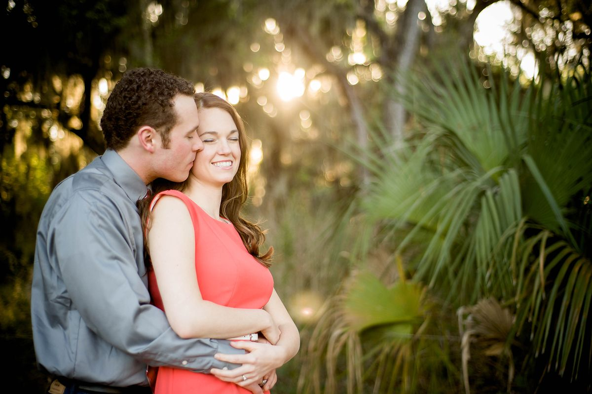 Man holding woman from behind kissing her cheek in golden glow at Circle B Lakeland, fl Wedding Photographer