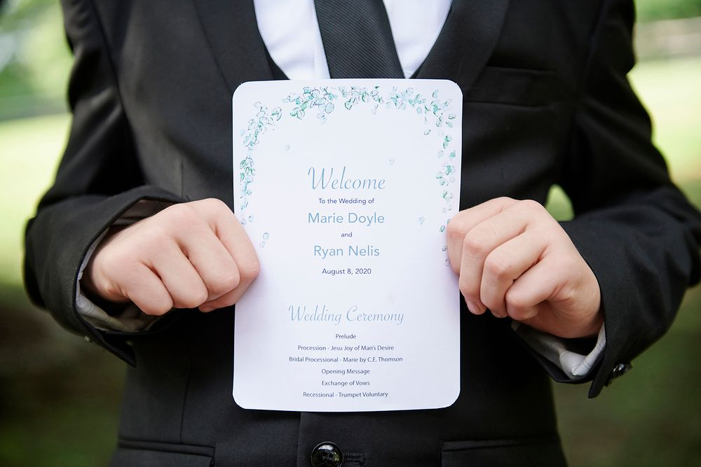 ring bearer holds wedding program at backyard micro wedding