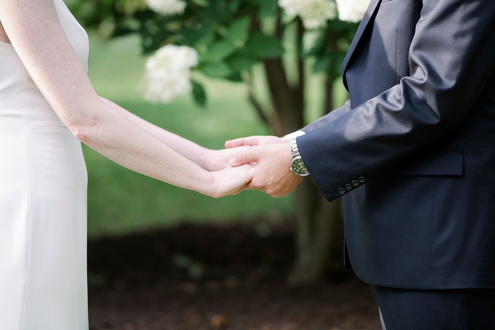 bride and groom hold hands during ceremony at backyard micro wedding