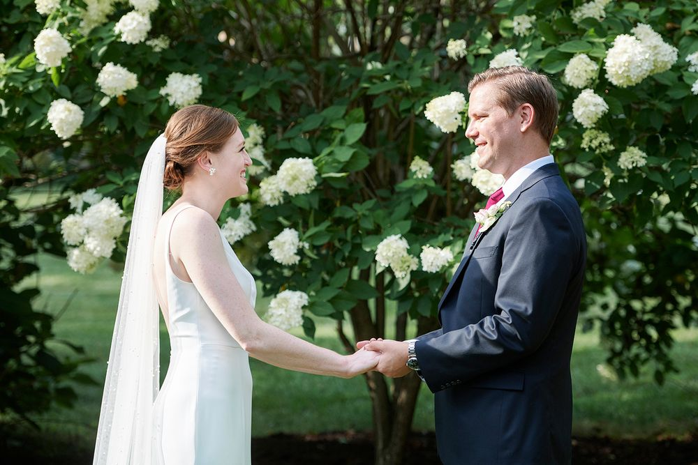 bride and groom hold hands at backyard micro wedding