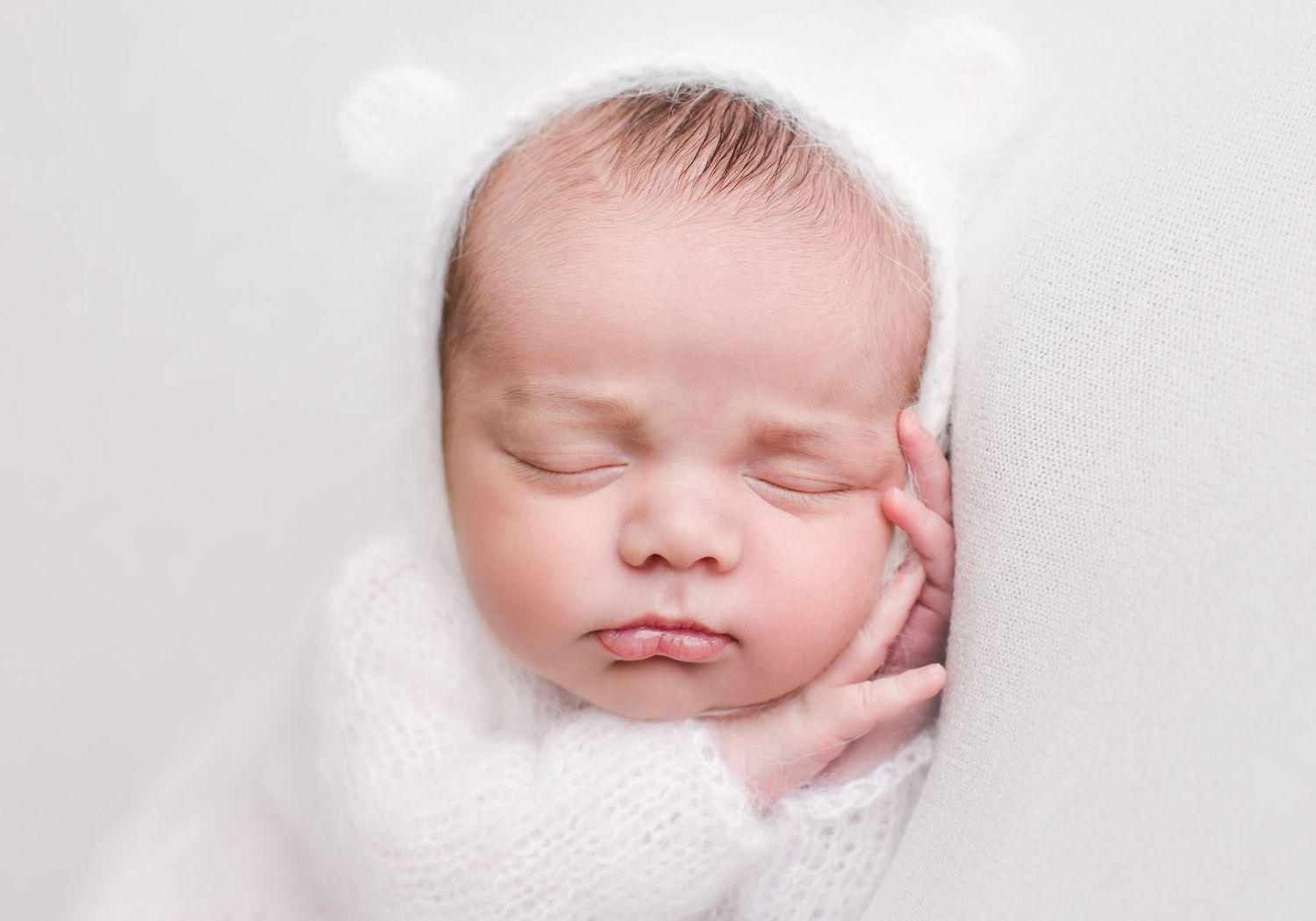 Newborn baby posed sleeping on white back drop - newborn photographer in penticton bc