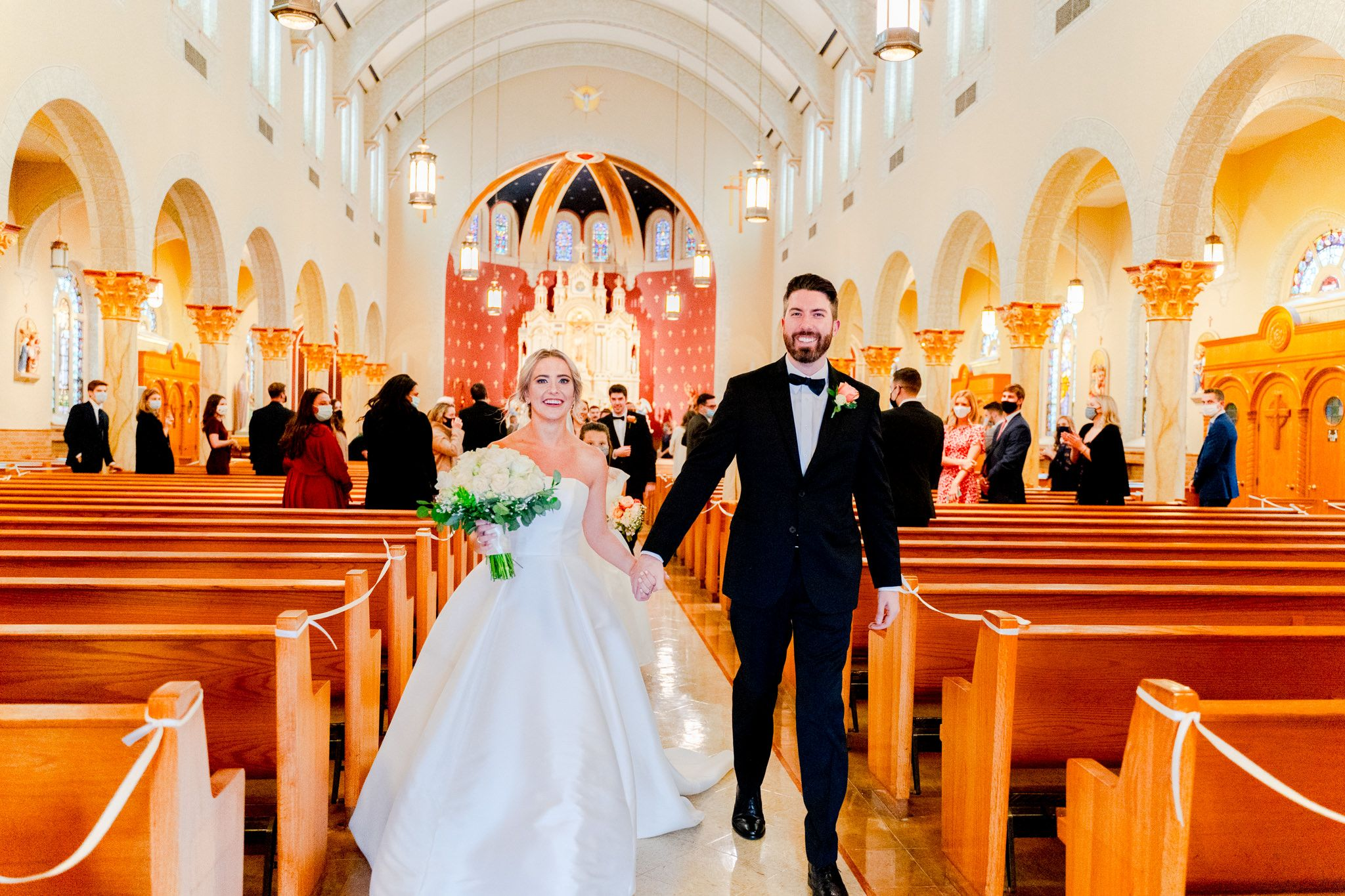 bride and groom walking down church aisle after being married, wedding guests in back smiling at them with masks on