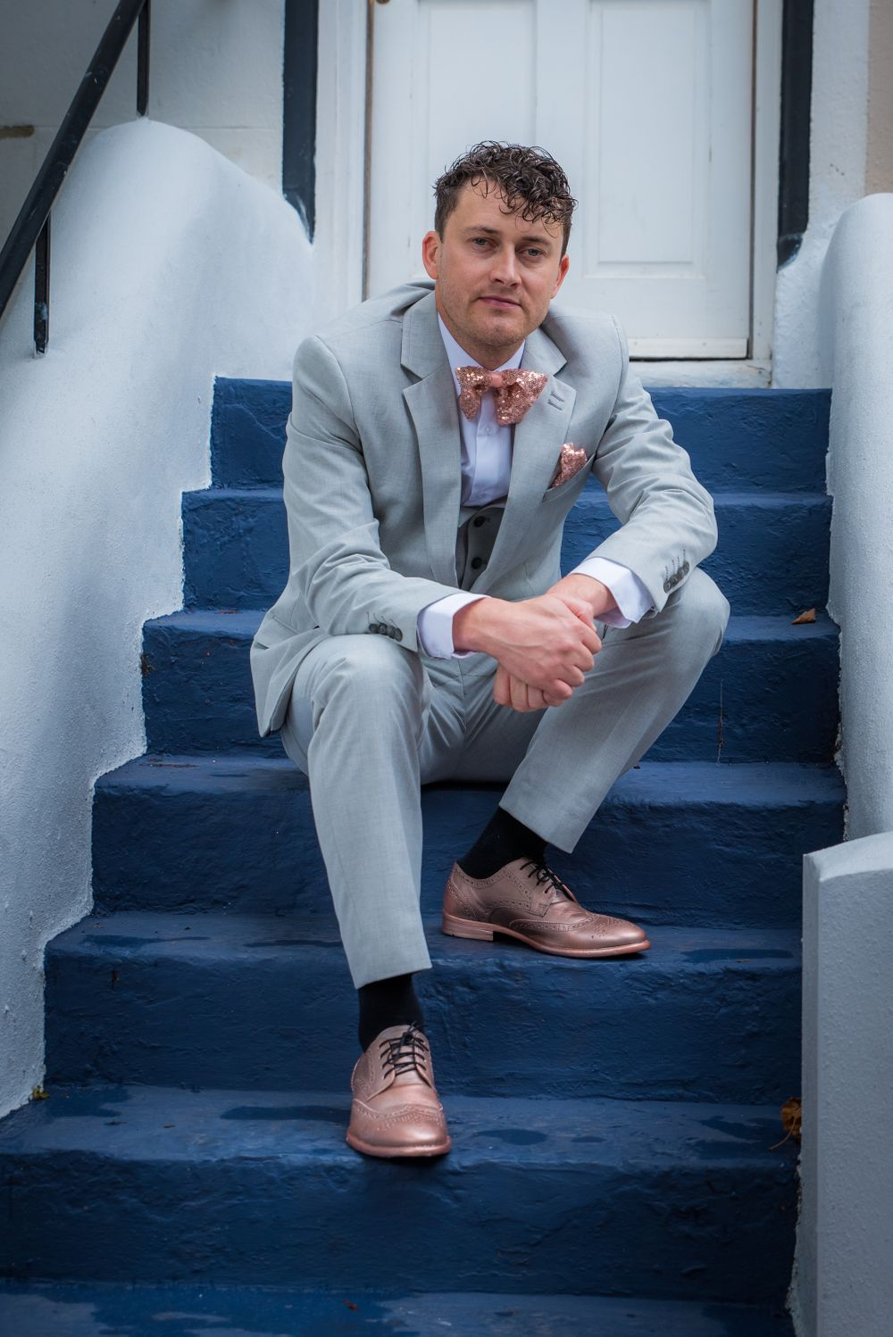 groom on blue steps in Brighton, Robert Nelson Wedding Photography