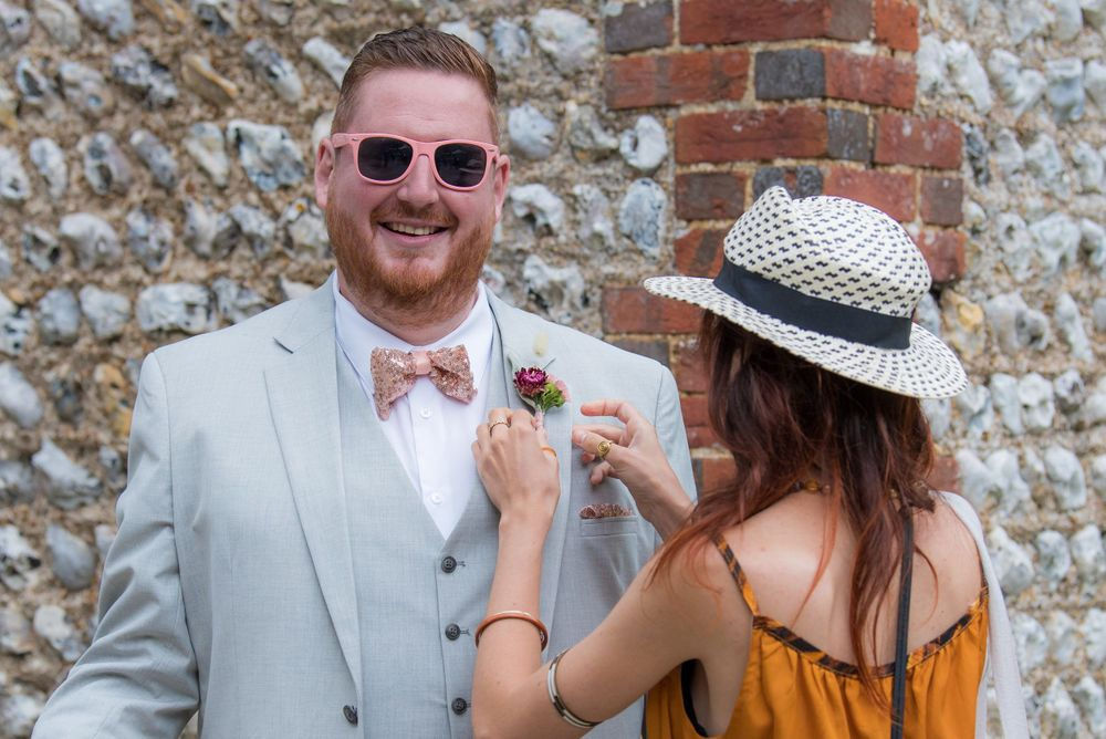woman putting on a button hole on best man