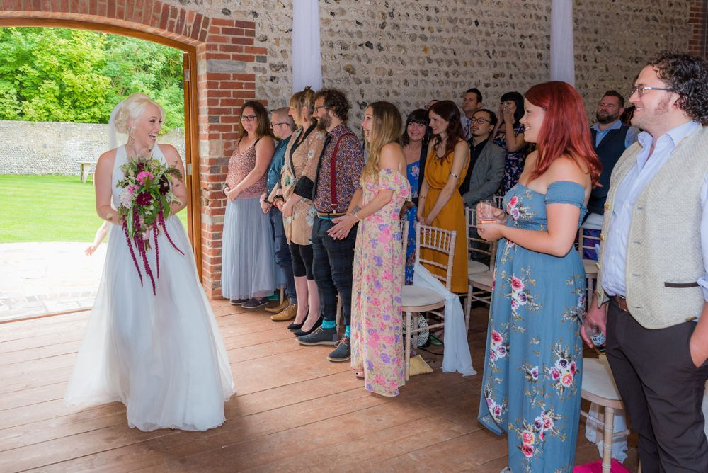 bride walking in to the ceremony at cissbury barns
